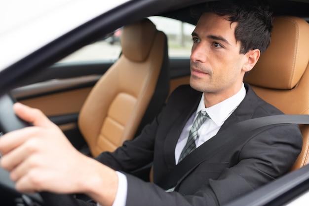 Glimlachende bedrijfsmens die zijn nieuwe witte auto drijft