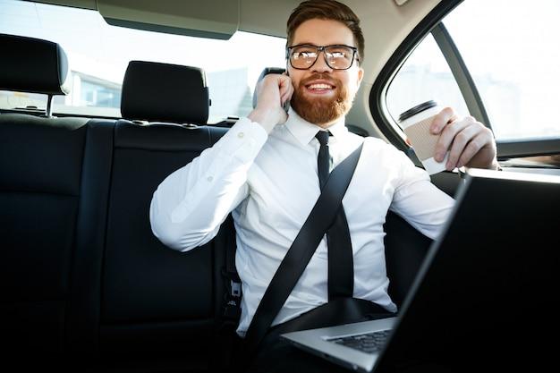 Glimlachende bedrijfsmens met laptop die op telefoon spreekt