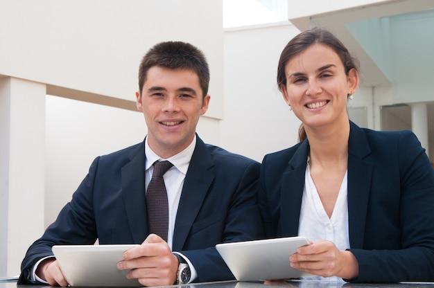 Glimlachende bedrijfsmensen die camera bekijken en tabletten houden