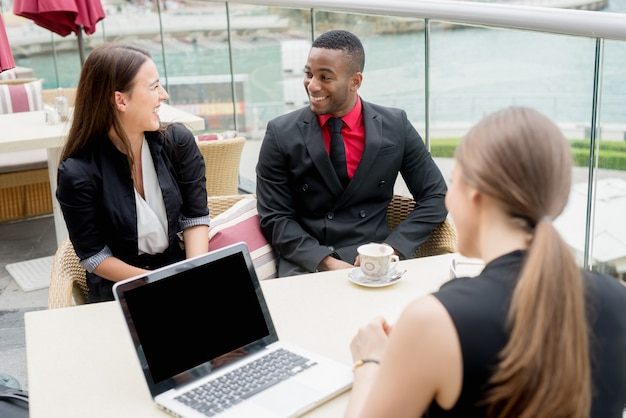 Glimlachende bedrijfsmensen die een openluchtvergadering hebben. succesvolle lopende regelingen. brainstormen.