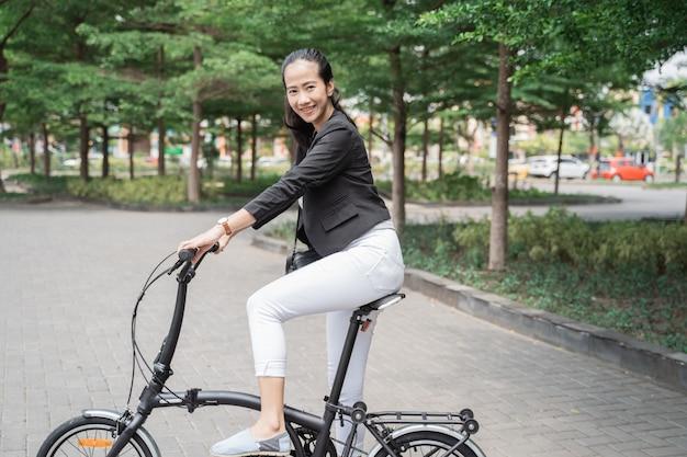 Glimlachende bedrijfsvrouw die haar vouwfiets berijden