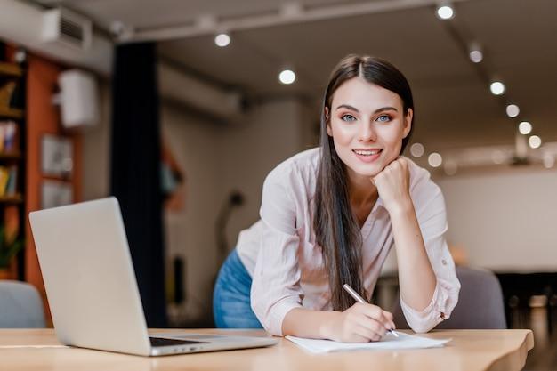 Glimlachende bedrijfsvrouw die in modern bureau documenten en het glimlachen ondertekent
