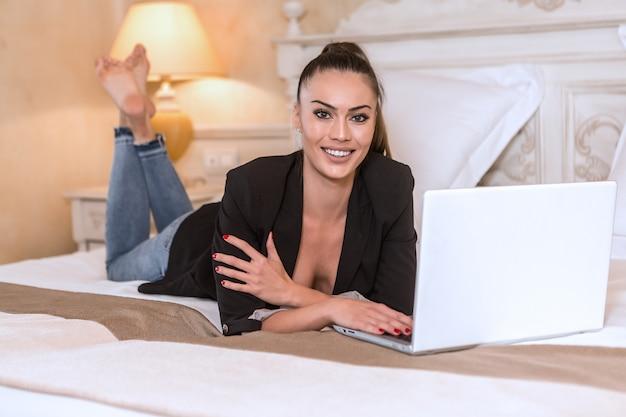 Glimlachende bedrijfsvrouw die met witte laptop ligt