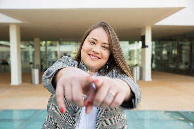 Glimlachende bedrijfsvrouw die vingers op camera in openlucht richten