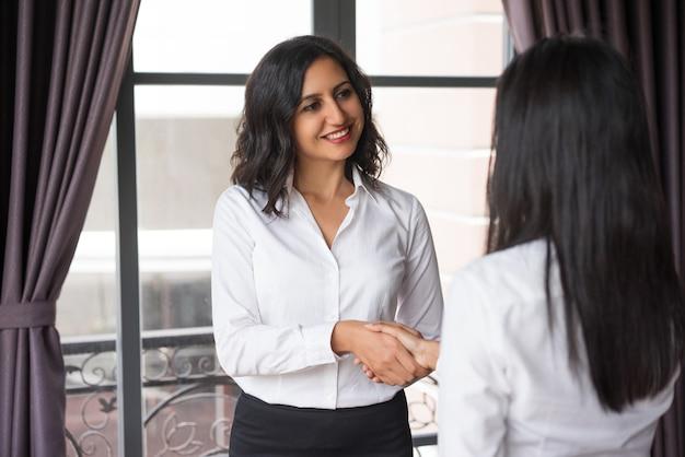 Glimlachende bedrijfsvrouw het schudden handen met partner bij koffievenster