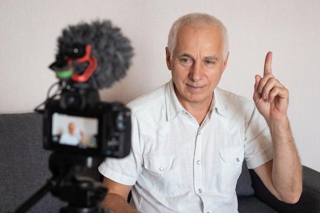 Glimlachende bejaarde die camera bekijkt die videoblog op bank headshot maakt