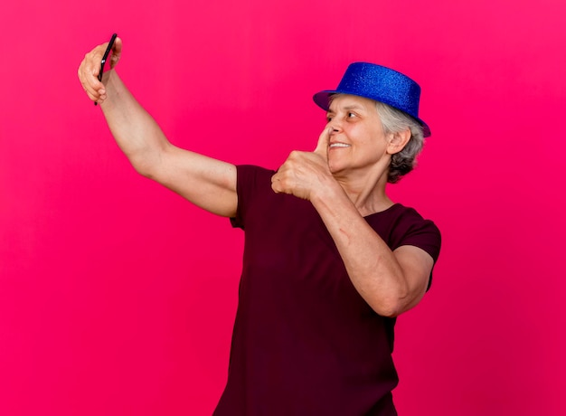 Glimlachende bejaarde die partijhoed draagt ?? die omhoog houdt en naar telefoon kijkt op roze