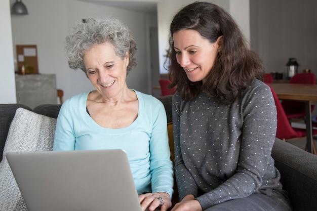 Glimlachende bejaarde en haar dochter die op laptop doorbladeren
