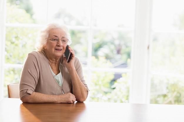 Glimlachende bejaarde telefoon die thuis roept