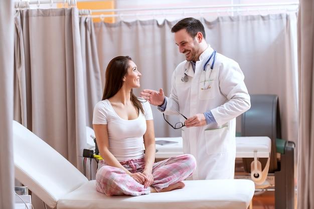 Glimlachende beleefde dokter in wit uniform praten met vrouwelijke patiënt. vrouw zittend op het bed met gekruiste benen.