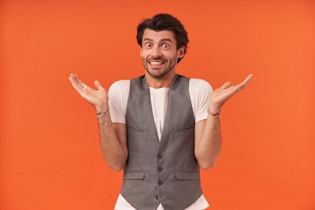 Glimlachende beschaamde jonge man met stoppels die copyspace op twee handpalmen houdt en schouders ophaalt