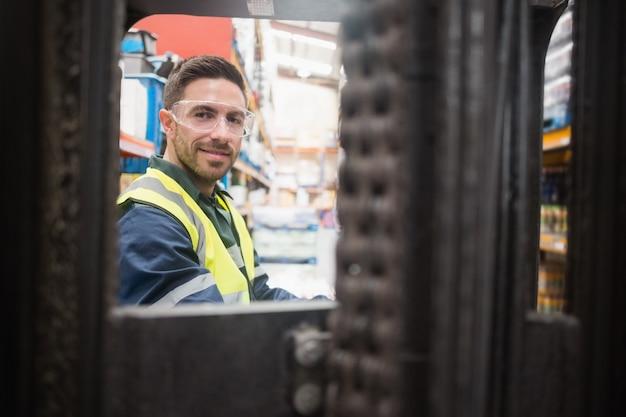 Glimlachende bestuurder werkende vorkheftruckmachine