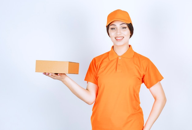 Glimlachende bezorger die doos in de lucht houdt en naar de voorkant kijkt