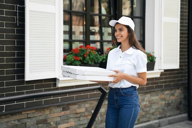 Glimlachende bezorger die dozen pizza draagt
