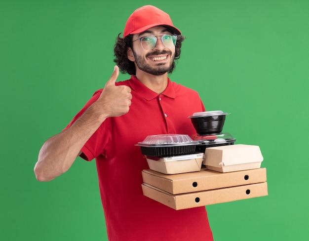 Glimlachende bezorger in rood uniform en pet met een bril met pizzapakketten met papieren voedselpakketten en voedselcontainers erop kijkend naar de voorkant met duim omhoog