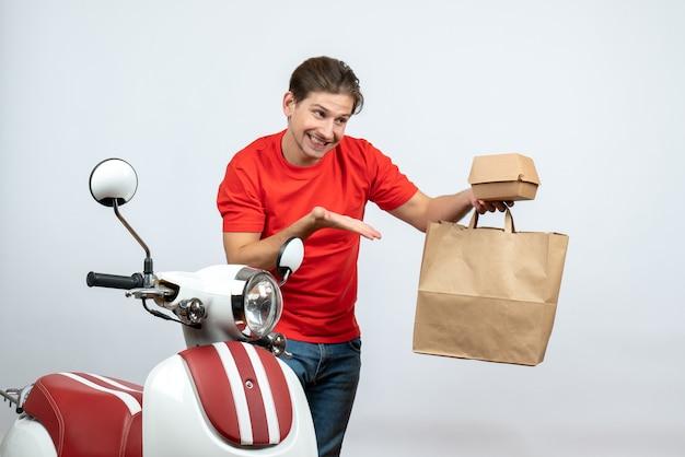 Glimlachende bezorger in rood uniform staande in de buurt van scooter en bestellingen tonen op witte achtergrond