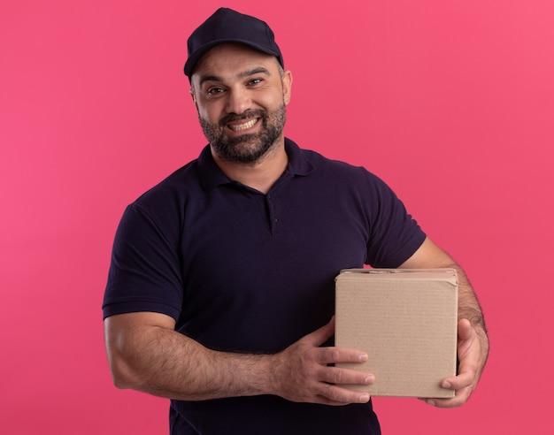 Glimlachende bezorger van middelbare leeftijd in uniform en dop met doos geïsoleerd op roze muur