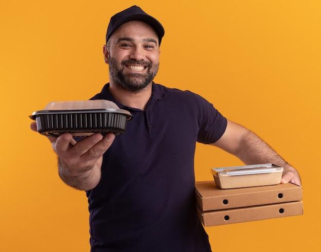 Glimlachende bezorger van middelbare leeftijd in uniform en pet die pizzadozen houdt en voedselcontainer standhoudt die op gele muur wordt geïsoleerd