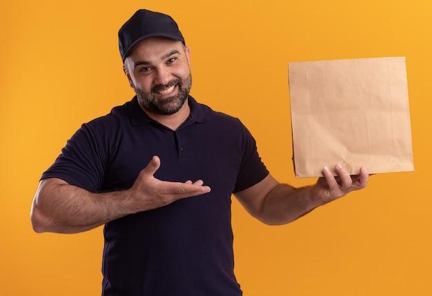 Glimlachende bezorger van middelbare leeftijd in uniform en pet in de hand en wijst naar een papieren voedselpakket geïsoleerd op een gele muur