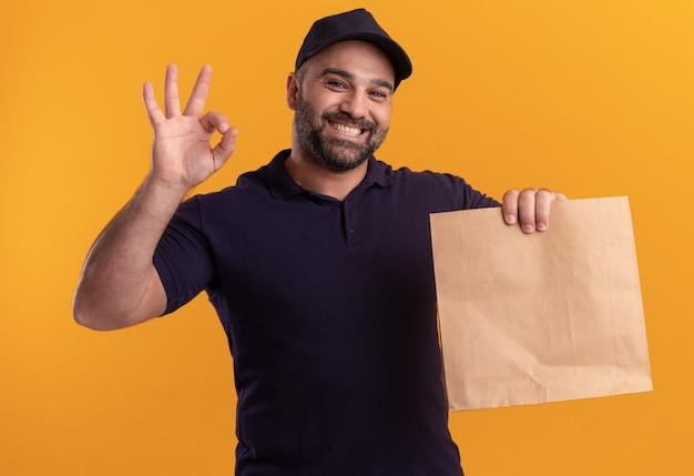 Glimlachende bezorger van middelbare leeftijd in uniform en pet met papier voedselpakket met ok gebaar geïsoleerd op gele muur