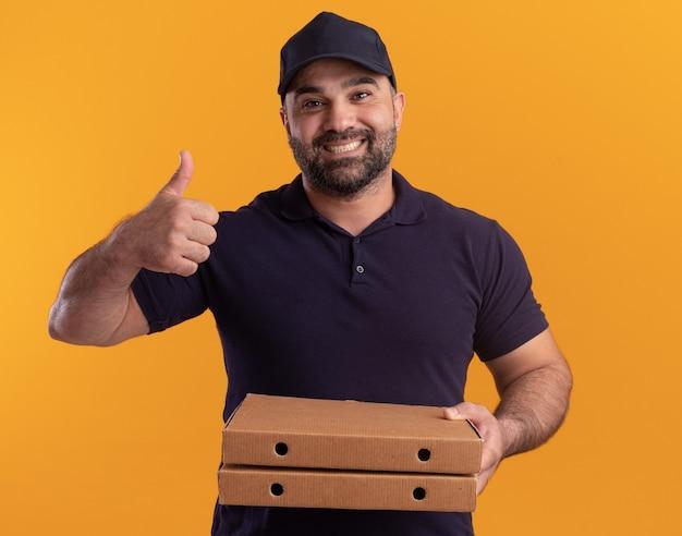Glimlachende bezorger van middelbare leeftijd in uniform en pet met pizzadozen die duim tonen die omhoog op gele muur wordt geïsoleerd