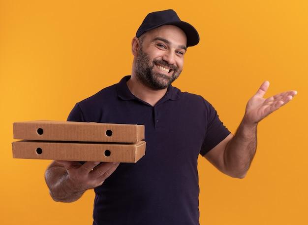 Glimlachende bezorger van middelbare leeftijd in uniform en pet met pizzadozen die hand verspreiden die op gele muur wordt geïsoleerd
