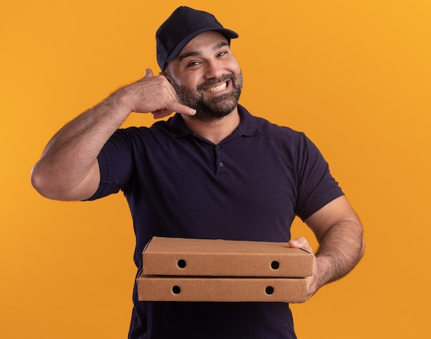 Glimlachende bezorger van middelbare leeftijd in uniform en pet met pizzadozen die telefoongesprekgebaar tonen dat op gele muur wordt geïsoleerd