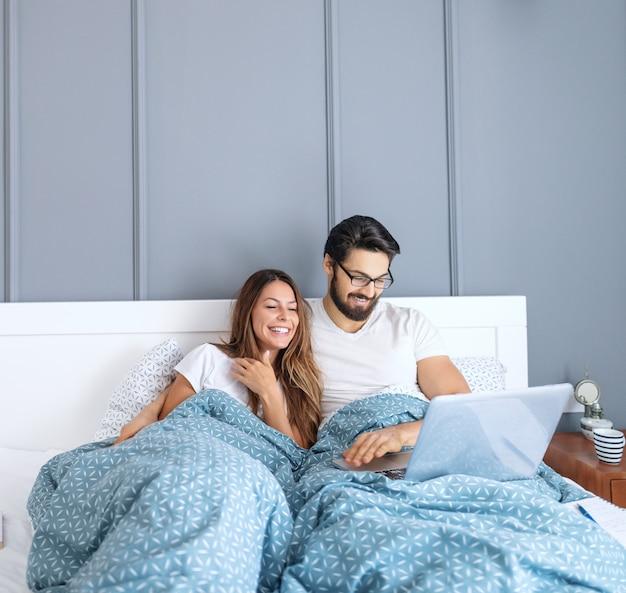 Glimlachende blanke bebaarde man met bril met behulp van laptop en knuffelen zijn vrouw. ochtend tijd.
