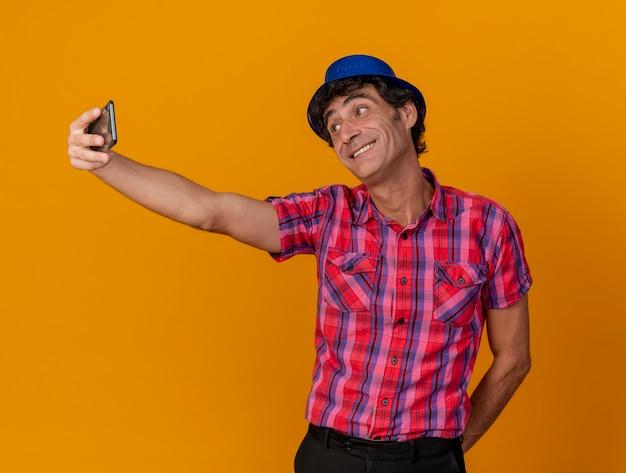 Glimlachende blanke feestmens van middelbare leeftijd met feestmuts die hand achter rug houdt die selfie neemt geïsoleerd op een oranje achtergrond