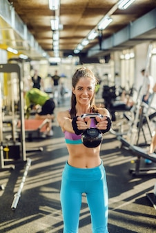 Glimlachende blanke fit vrouw met paardenstaart en gekleed in sportkleding kettlebell opheffen terwijl staande in de sportschool.