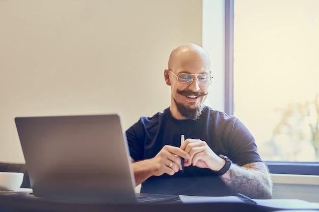 Glimlachende blanke kale man-manager die laptop gebruikt tijdens het schrijven van notities in notitieblok op de werkplek