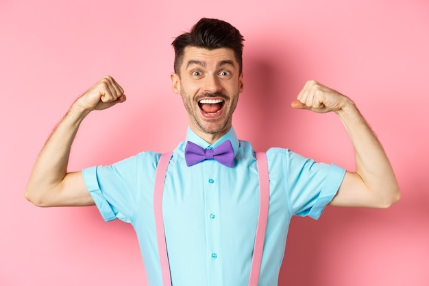 Glimlachende blanke man met vlinderdas en bretels, toont spieren en voelt zich sterk, buigt biceps om te pronken, staande over roze achtergrond.