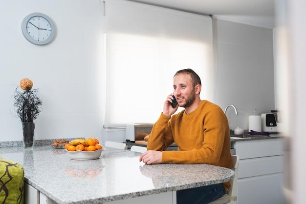 Glimlachende blanke man zit aan de keukentafel met fruit en praat aan de telefoon