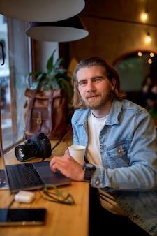 Glimlachende blanke mannelijke ontwerper bezig met marketingproject in café, bekwame knappe fotograaf die ideeën opmerkt om geld te verdienen bij het bewerken van afbeeldingen op laptop, in vrijetijdskleding, kijk naar de camera
