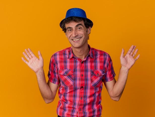 Glimlachende blanke partijmens van middelbare leeftijd die partijhoed draagt die camera bekijkt die lege die handen toont op oranje achtergrond wordt geïsoleerd