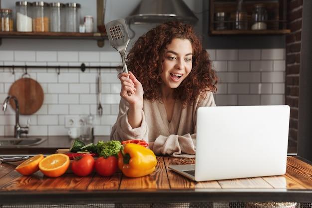 Glimlachende blanke vrouw die laptop gebruikt tijdens het koken van verse groentesalade in het keukeninterieur thuis