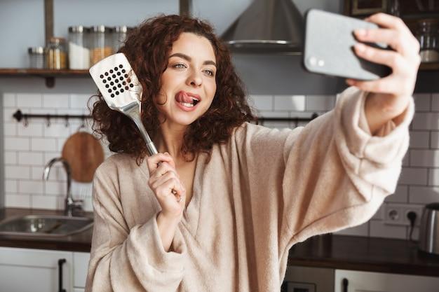 Glimlachende blanke vrouw die selfie foto neemt op smartphone tijdens het koken van verse groentensalade in het keukeninterieur thuis