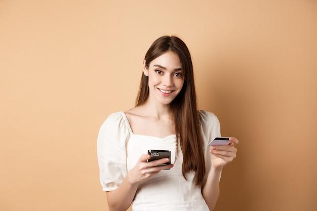 Glimlachende blanke vrouw die voor online bestelling betaalt, plastic creditcard en mobiele telefoon vasthoudt, zorgeloos naar camera kijkt, beige.