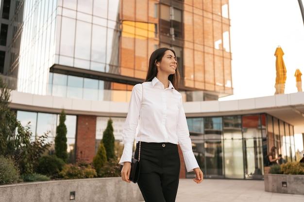 Glimlachende blanke vrouw in zakelijke kleding die in de buurt van het stedelijke zakencentrum loopt
