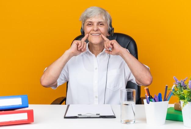 Glimlachende blanke vrouwelijke callcenter-operator op koptelefoon zittend aan bureau met kantoorhulpmiddelen die haar glimlach met vingers geïsoleerd op oranje muur houdt