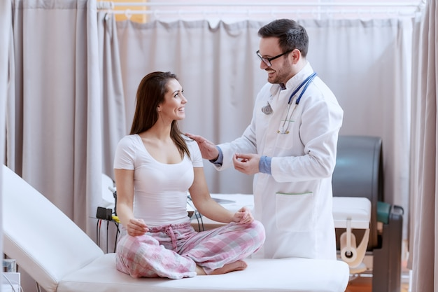 Glimlachende blanke vrouwelijke patiënt in pyjama zittend op ziekenhuisbed met gekruiste benen en luisteren naar arts. dokter die hand op vrouw schouder houdt en haar een goed nieuws vertelt.