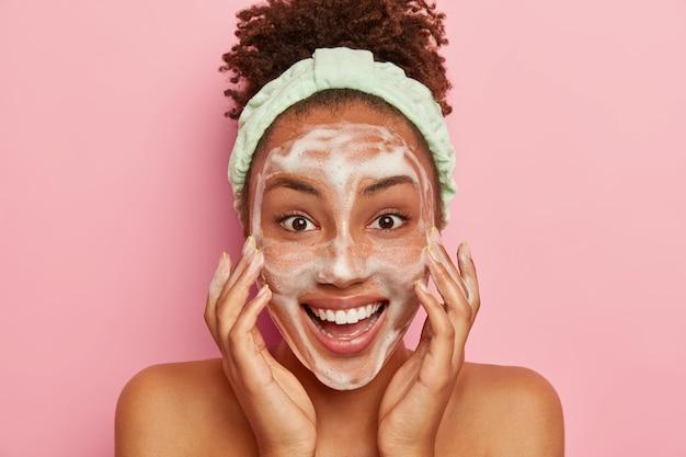 Glimlachende blije jonge vrouw met donkere huid zet zeep op gezicht om te reinigen, wast met koud water, wil een gezonde, frisse huid., draagt een hoofdband, ziet er positief uit, staat naakt binnen