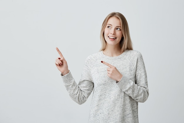 Glimlachende blije vrouw die met vinger op copyspace richt