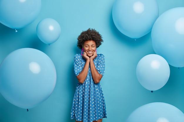 Glimlachende blije vrouw met donkere huid geniet van verjaardagsfeestje, staat met gesloten ogen en charmante glimlach, draagt mooie blauwe zomerjurk met stippen, wacht op gasten poses rond opgeblazen ballonnen, maakt foto