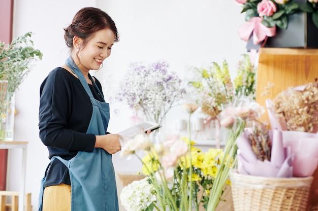 Glimlachende bloemist die bloemen in winkel controleert