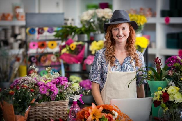 Glimlachende bloemist die laptop in bloemenwinkel met behulp van