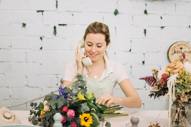 Glimlachende bloemist die op telefoon spreekt