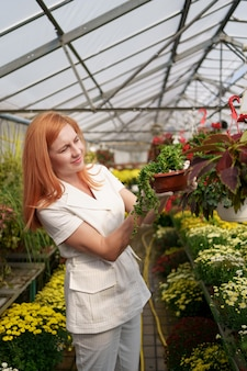 Glimlachende bloemist in haar kwekerij inspecteert potbloemen terwijl ze de tuinplanten in de kas verzorgt