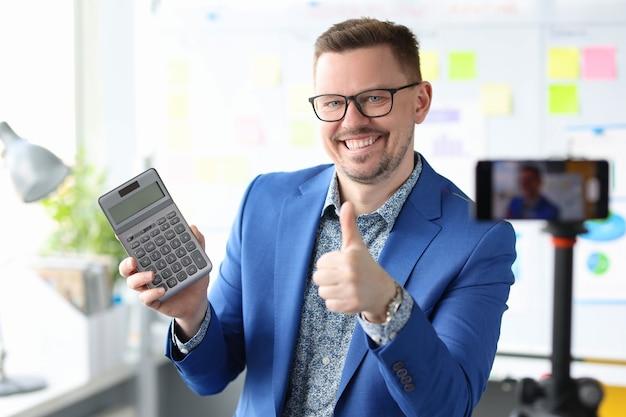 Glimlachende blogger-zakenman houdt een rekenmachine vast en neemt trainingsvideo's op over inkomsten