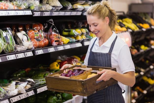 Glimlachende blonde arbeider die een doos met groenten houdt